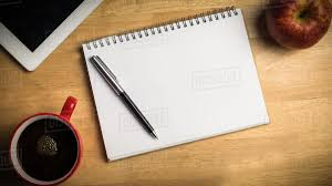 Overhead of notepad and pen on a cluttered desk - Stock Photo - Dissolve